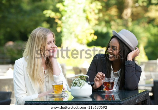 Two beautiful women drinking tea outdoors
