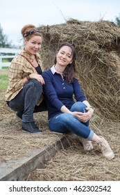 Two beautiful women a girlfriends sitting beside a stack of hay