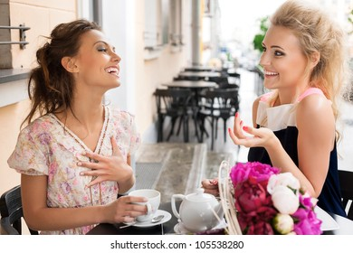 Two beautiful women with great smile and hairstyle sitting at a bar, drinking tea and coffee.