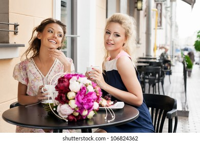 Two beautiful women with great smile and hairstyle sitting at a bar, drinking tea and coffee. outdoors