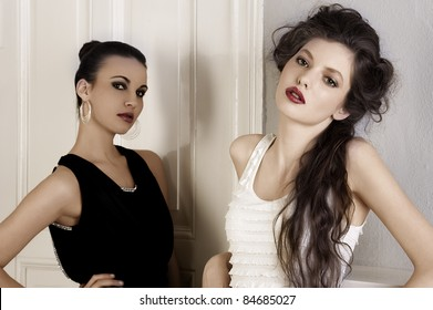 two beautiful women with hair style and elegant dress posing indoor near an old fashion door posing while looking towards camera