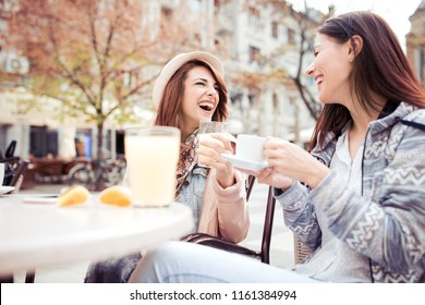 Two beautiful women having conversation,drinking coffee and sitting in cafe.