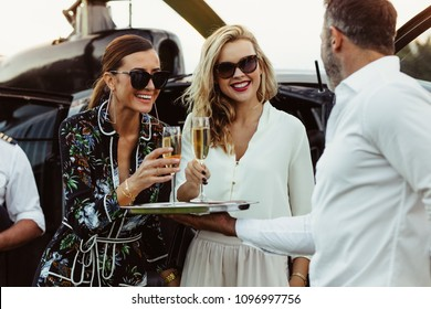 Two beautiful women having welcome drinks served by a male host. Man greets female friends with wine by a helicopter.