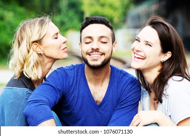 two beautiful women kissing handsome man on his cheeks