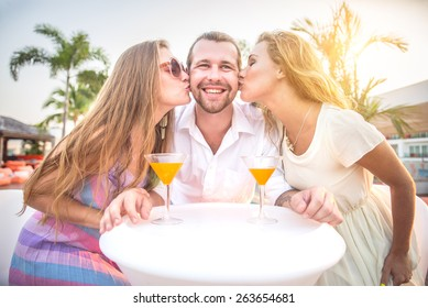 Two beautiful women kissing on cheeks a man - Friends at party drinking cocktails and having fun - Three tourists drinking aperitif in a tropical luxurious restaurant