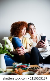 Two beautiful women, looking at mobile phone screen, smiling (selective focus)