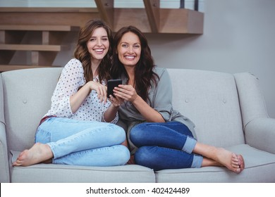 Two beautiful women looking at the mobile phone at home