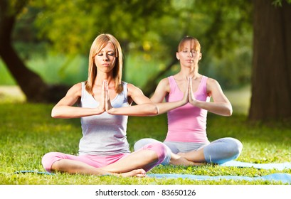Two beautiful women meditating in the park