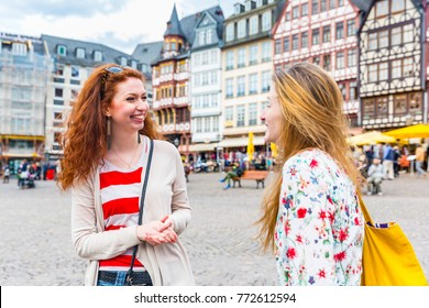 Two beautiful women meeting and having fun in Frankfurt main square. Girls smiling and chatting with houses and people on background. Friendship and travel concepts.