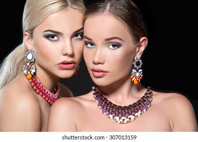 Two beautiful women with necklace and earrings. Jewelry and beauty