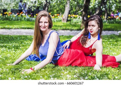 Two beautiful women on the grass in the park