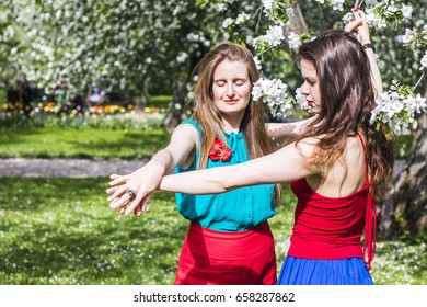 Two beautiful women outdoors on the flowering forest background