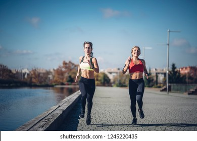 Two beautiful women perform outdoor exercise in park.