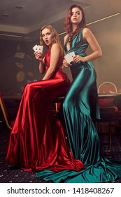 Two beautiful women are posing against a poker table in luxury casino.