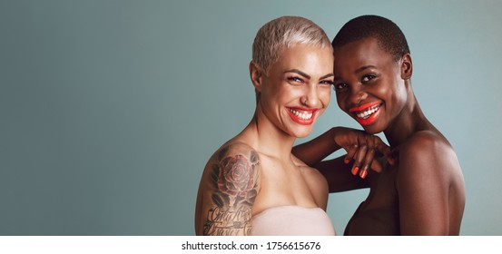 Two beautiful women standing together against gray background. Female models of different ethnicities with colorful makeup looking at camera and smiling.