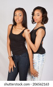 Two beautiful women standing together and looking at the camera with a serious expression