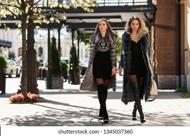 Two beautiful women in sun glasses and fur coat, smiling, posing with luxury bags and accesories while standing and walking outdoors. Female fashion city lifestyle spring or autumn shopping concept