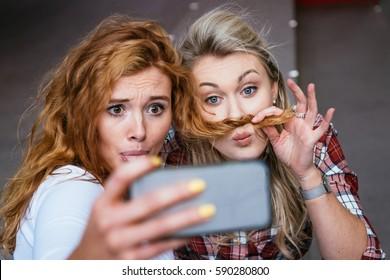 Two beautiful women taking a funny selfie