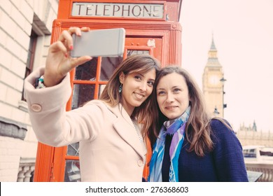 Two beautiful women taking a selfie in London with Big Ben and red phone booth on background. They are in their twenties, holding the phone and looking at it. Focus on the face.