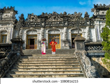 two beautiful women with Vietnam culture traditional dress hold hat walking at the staircase looking back in ancient city