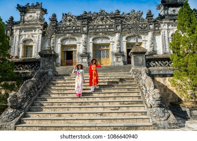 two beautiful women with Vietnam culture traditional dress hold hat walking at the staircase looking back in ancient cityTomb of Tu Duc emperor in Vietnam