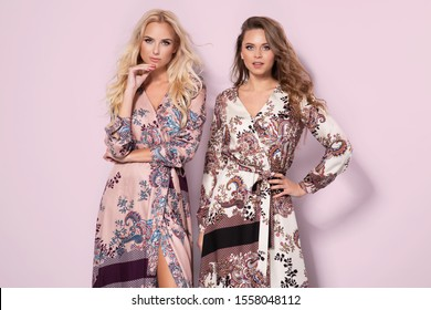 Two beautiful women wearing nice long dresses. Portrait of happy smiling girls in stylish glamorous clothes. Autumn spring fashion photo on pink background.