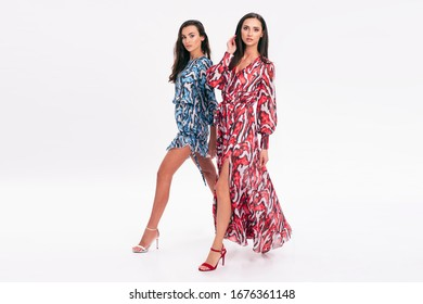 Two beautiful women wearing nice clothes. Portrait of happy smiling girls in stylish glamorous dresses. Spring summer fashion photo on a white background.