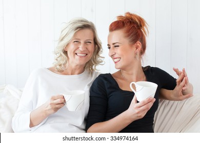 Two beautiful women-a mother and daughter sitting on the sofa at home, snuggled. They drink coffee, tea. Relationships and shared time.