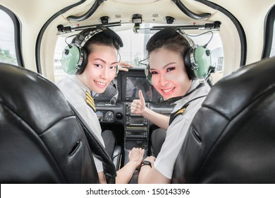 two beautiful young Asian pilot student looking at the back seat holding up thumb, wearing their uniform and headsets. In small light aircraft ready to take off