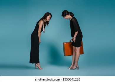 Two beautiful and young Asian women bow to one another against a blue studio background. They are displaying mutual respect for one another and are both dressed in smart casual.