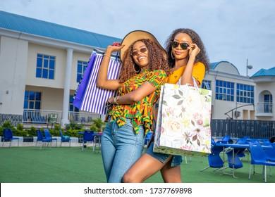 two beautiful young black women posing shopping bags