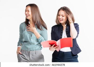 Two beautiful young brunette business women, laughing