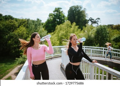 Two beautiful young caucasian girls drink water after training in nature