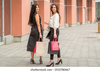 Two beautiful young caucasian happy women with shopping bags walk into the shopping mall