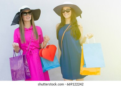 Two beautiful young cheerful women holding shopping bags and looking at the camera.  Beautiful girls with shopping bags standing in front of a white wall. Lens flare in the background.