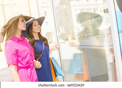 Two beautiful young cheerful women holding shopping bags and looking at the shop window.  Beautiful girls with shopping bags walking in a city center.