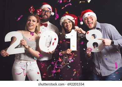 Two beautiful young couples having fun at New Year's Eve Party, holding cardboard numbers 2018