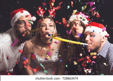 Two beautiful young couples having fun at New Year's party, dancing and blowing party whistles