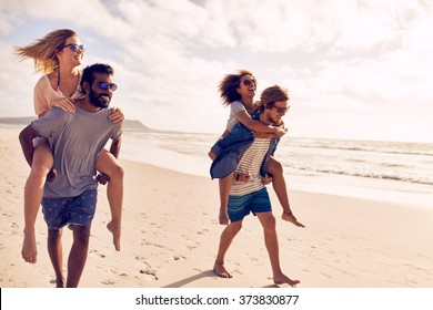Two beautiful young couples walking by the beach, with men carrying their women on their back. Couples piggybacking on sea shore. Having fun on beach vacation.