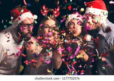 Two beautiful young couples wearing Santa hats, blowing away colorful confetti at midnight at New Year's Eve party