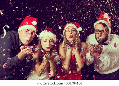 Two beautiful young couples wearing Santa's hats, blowing colorful confetti at midnight at New Year's Eve party
