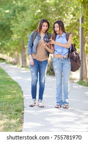 Two Beautiful Young Ethnic Twin Sisters With Backpacks Using A Smartphone Outside.