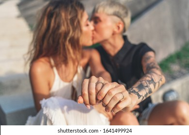 Two beautiful young female bride women, lesbian wedding, beauty fashion and rights lgbt concept, tenderness hugs kisses, hands with rings close-up.