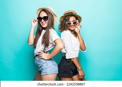 Two beautiful young girl friends in sunglasses and straw hat posing with smile and have a fun on blue background