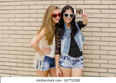 Two beautiful and young girlfriends taking pictures, in front of a brick wall
