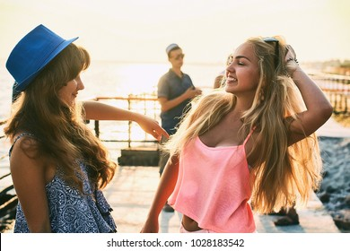 Two beautiful young girls brunette and blonde smiling and having fun at the seaside with group of their friends one of them with guitar