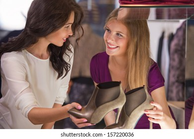 Two beautiful young girls choosing shoes at store. Holding pair near showcase and speaking