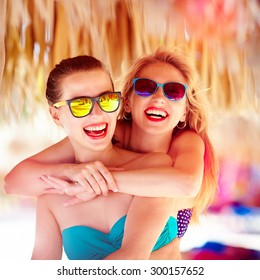 two beautiful young girls having fun on beach during summer vacation