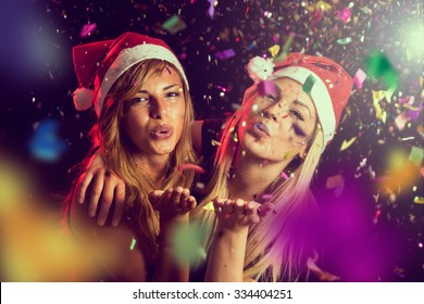 Two beautiful young girls having fun at New Year's Eve party, sending kisses