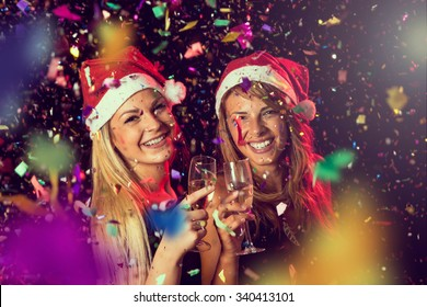 Two beautiful young girls having fun at New Year's Eve party, toasting each other at midnight